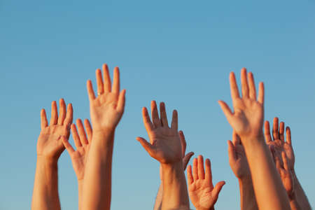 Ten raised up sunlit adult hands on the blue sky background