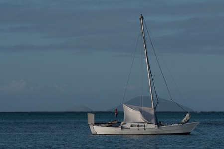 A white boat setting sail in the open sea Фото со стока