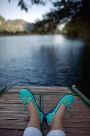 A lake view with a fragment of a boat and two feet in turquoise shoes Stock Photo