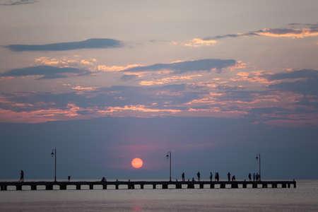 A long city pier with streetlights and walking people, meeting sunset Фото со стока