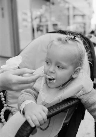 A baby girl sitting in her stroller and being fed with yogurt by her mothers hand