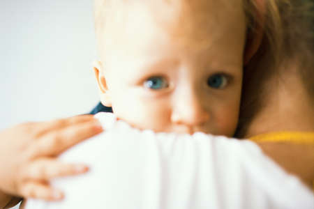 An unfocused portrait of a blue-eyed baby, hugging its mother, who is holding it in her arms Фото со стока