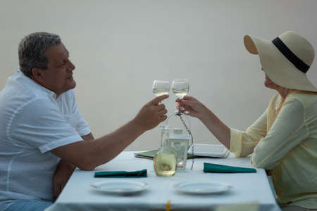 A middle-aged couple sitting at a laid table, clinking glasses with white wine and waiting for entrees