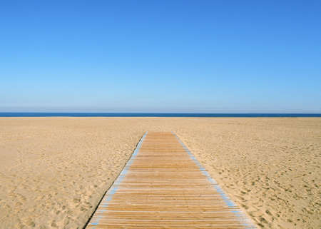 A yellow-blue picture, where the blue half is sky and the yellow half is sand and a wooden path on it. A thin dark blue line of sea in the middle