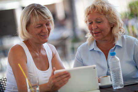 Two smiling senior women are sitting close to each other at a table of an outdoor cafe. They are both looking at the tablet that one of the women is holding in a hand. There are a bottle of water, a glass with a straw and a cup of coffee on the table