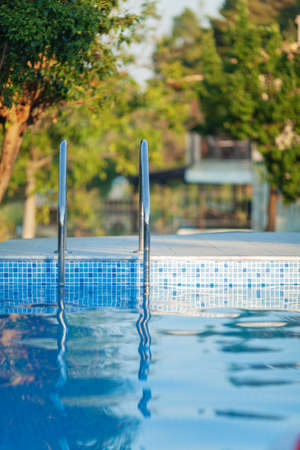 An open swimming pool with clean glossy water and a shiny metal railing. There are green trees on a blurred background, lightened up with a warm evening sun