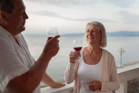 A smiling middle aged couple on a terrace holding glasses of red wine. They are smiling looking at each other. There is a beautiful blurred sea view behind them Фото со стока