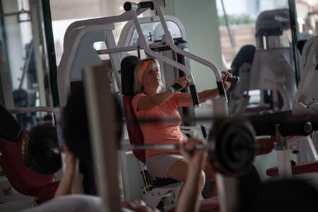 A fair haired senior woman in an orange T shirt and with an orange hair band is working out in the gym. She is using one of the training machines Фото со стока