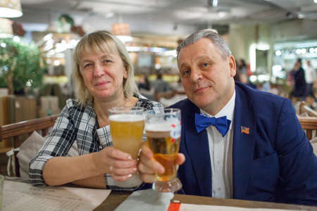 A portrait of a middle aged couple sitting at the table close to each other. Man is wearing a blue jacket and a bright blue bow tie. A woman is in a checkered shirt. Both of them are raising glasses of beer and smiling Фото со стока