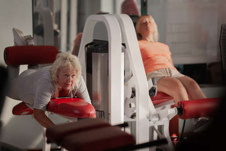 Two middle aged fair haired women are working out in the gym. They are using gym equipment next to each other. Both of them are looking tired but dedicated Фото со стока