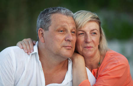 A portrait of a smiling middle aged couple. A man in a white shirt and a fair haired woman in an orange one are looking into the distance, sitting close to each other and smiling slightly. The woman is leaning oh husbands shoulder