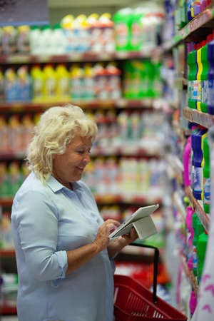 A middle aged fair haired woman is standing in a household section of a supermarket, close to the shelves. She is looking at a tablet screen holding it in hands and smiling