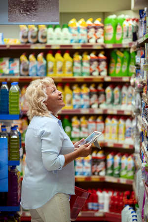 A smiling middle aged woman in a light blue shirt is standing in a household section of a supermarket. She is holding a tablet and a red shopping basket in her hands. A woman is looking at the shelves, searching for something particular