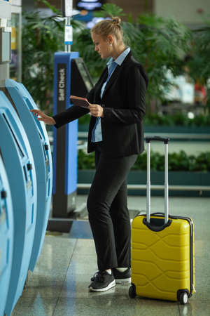 A young fair haired woman is standing near the self check terminal in an airport. She is holding her opened passport in one hand and entering data with another. There is a bright yellow suitcase near her