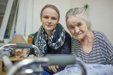 A portrait of a young fair haired woman sitting close to the elderly lady whose hand is on her arm. Both of them are slightly smiling