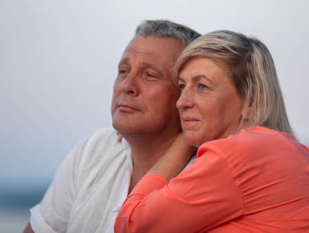 A middle aged couple, a man in a white shirt and a woman in an orange one, are sitting close to each other and looking into the distance with gentle smiles. Their heads are touching as the woman is leaning on her husbands shoulder Фото со стока