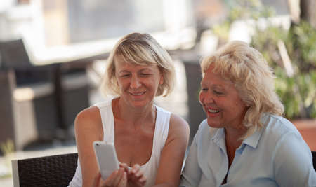 Two middle aged women are sitting outside at the table on a sunny day. They are both smiling while looking at a smartphone screen that one of the women is holding in hands