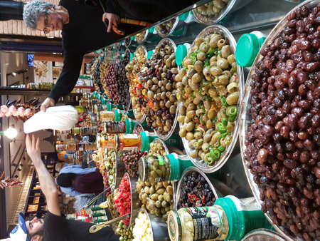 TEL AVIV, ISRAEL - MARCH 11, 2017: At the famous food market Sarona. View with great assortment of olives and buyer getting food Редакционное