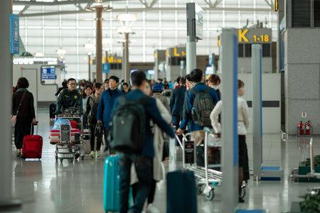 SEOUL, SÜDKOREA - 26. OKTOBER 2015: Menschen mit Koffern und Gepäckwagen am internationalen Flughafen Incheon. Er wurde von 2005 bis 2016 als bester Flughafen weltweit eingestuft