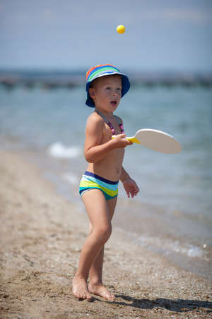 Funny and active child wearing summer hat and beads playing tennis on the beach near the sea. Fun and leisure on summer vacation