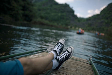 Man relaxing and enjoying landscapes with limestone mountains during the water tour in Trang An, Vietnam. View to the crossed feet on the boat Фото со стока