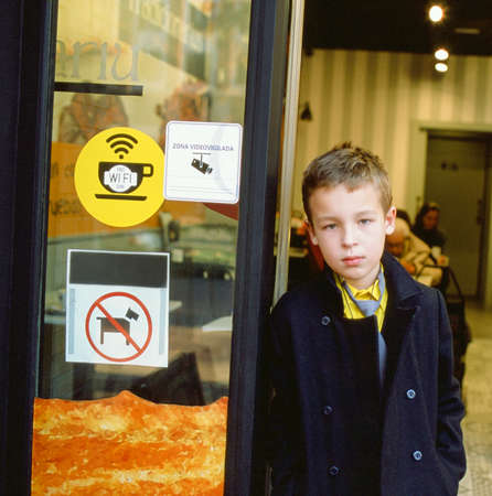 Serious schoolboy at the cafe entrance. Door with sticker signs of free wi-fi, video camera surveillance and animals forbidden. Spain
