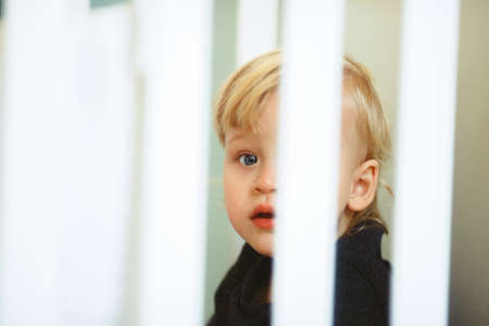 Close-up shot of blue-eyed baby girl with fair hair, view through the crib bars
