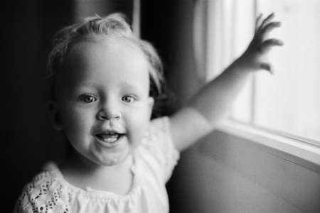 Black and white indoor portrait of smiling baby girl of one year old. Retro style shot