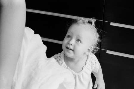 Black and white shot of lovely baby girl of one year old looking at mother with big curious eyes