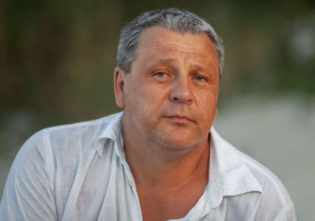Portrait of a mature man in white summer shirt against nature background Фото со стока
