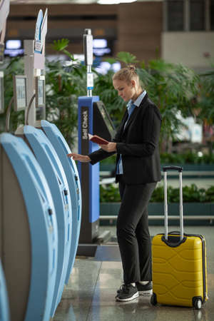 Woman traveler with ID using check-in terminal at the airport. Self-service kiosks Фото со стока