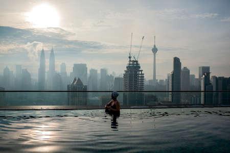 Woman enjoying cityscape of Kuala Lumpur from rooftop swimming pool. Urban scene with skyscrapers, Petronas Tower and Kuala Lumpur Tower, Malaysia