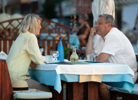 Mature couple on the date. Man and woman having nice time together in outdoor cafe and looking at each other