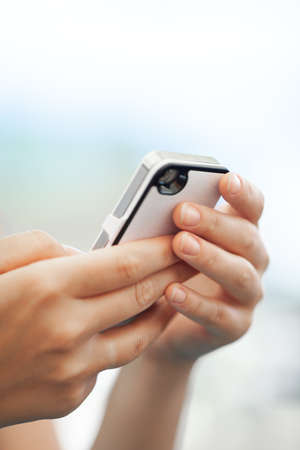 Close-up shot of woman with cell outdoor. Using smart phone for chatting, surfing the net and social media Фото со стока