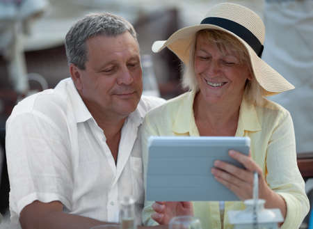 Happy mature couple with digital tablet watching photos or surfing the net together Фото со стока