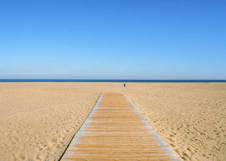 Scene of sea, sky and empty beach with soft sand, wooden pathway and waste container
