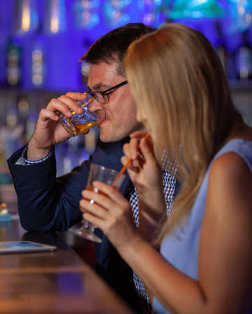 Young man and woman relaxing in the bar and having drinks. Nightlife and hanging out