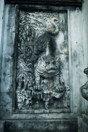 Ancient bas-relief with depiction of tiger on the wall of Temple of Literature in Hanoi, Vietnam