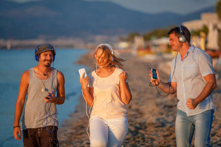 Group of three young friends enjoying the walk on the beach and excited with music. People with mobiles listening favorite songs in headphones