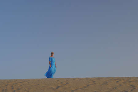 Young blond woman in long blue dress and sunglasses standing barefoot on the sand against clear sky