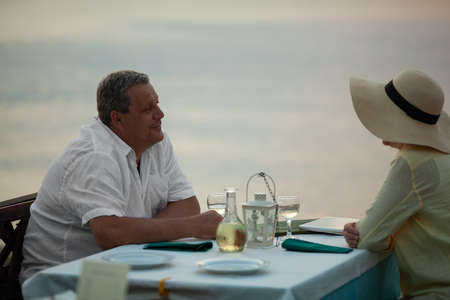 Mature couple having romantic evening. They enjoying the time and looking at each other sitting at the table in waterfront restaurant