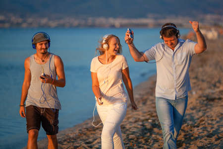 Excited friends outdoor. Young people relaxing and having fun listening to music in headphones Фото со стока