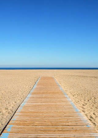Wooden pathway leading to the beach and sea. Summer scene with clear blue sky