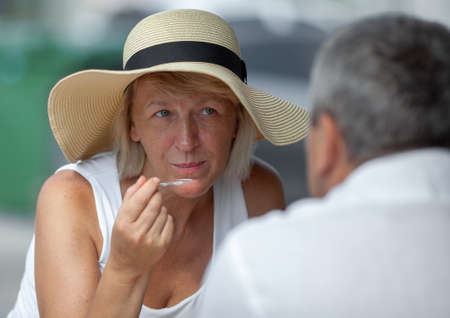 Mature blond woman in summer hat looking at her husband while having lunch in street cafe Фото со стока