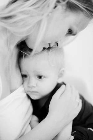 Black and white shot of mother comforting sad baby daughter. She embracing little child expressing love and care