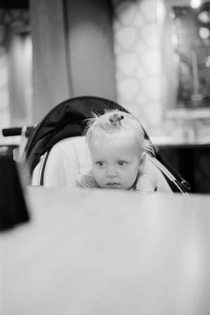 Black and white shot of one year cute baby girl sitting in stroller and watching cartoons on smart phone