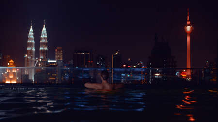 Night view of woman bathing in rooftop swimming pool and looking at the city with illuminated Petronas Towers and Kuala Lumpur Tower, Malaysia