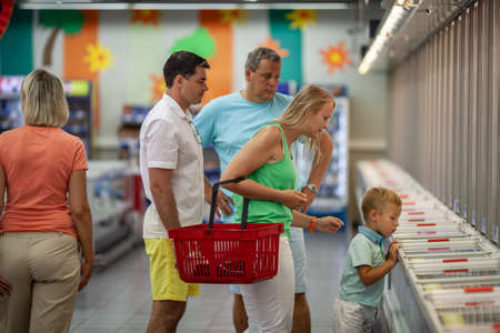 Big family with parents, grandparents and child shopping for food in the supermarket. Little boy exploring the freezers Фото со стока