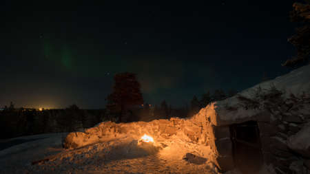Winter view of fire near the hut and Northern lights in dark night sky, Finland