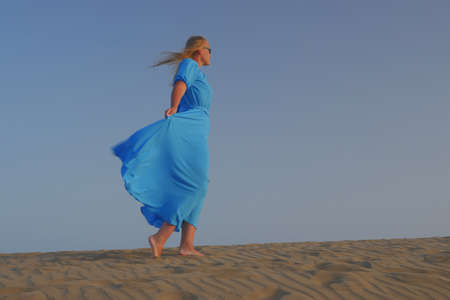 Young blond woman walking barefoot on the sand against clear sky. Her long blue dress fluttering in the wind Фото со стока